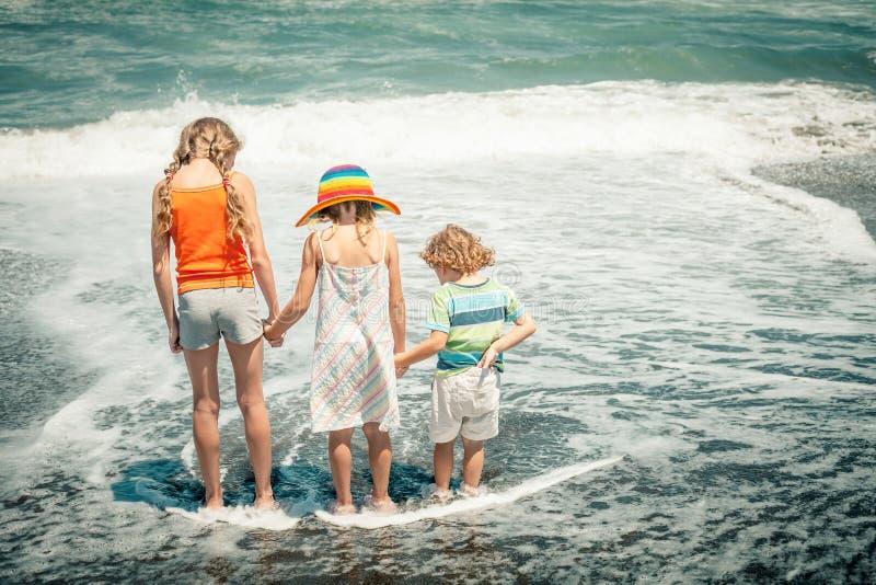 Tres niños felices que juegan en la playa fotos de archivo