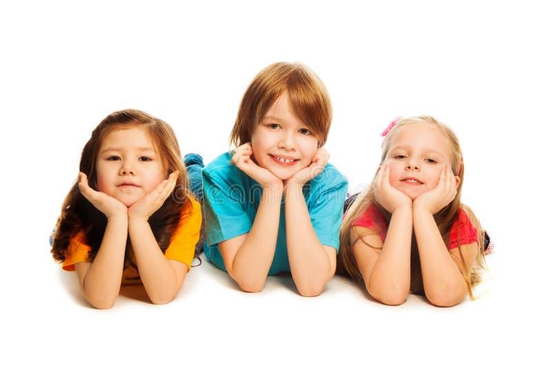 Tres niños en el suelo fotos de archivo