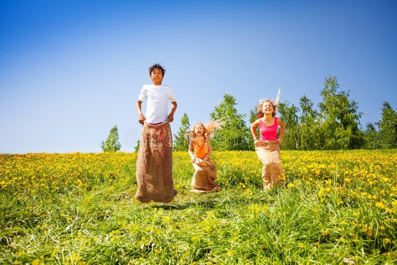 Tres niños felices que saltan en sacos durante juego imagenes de archivo