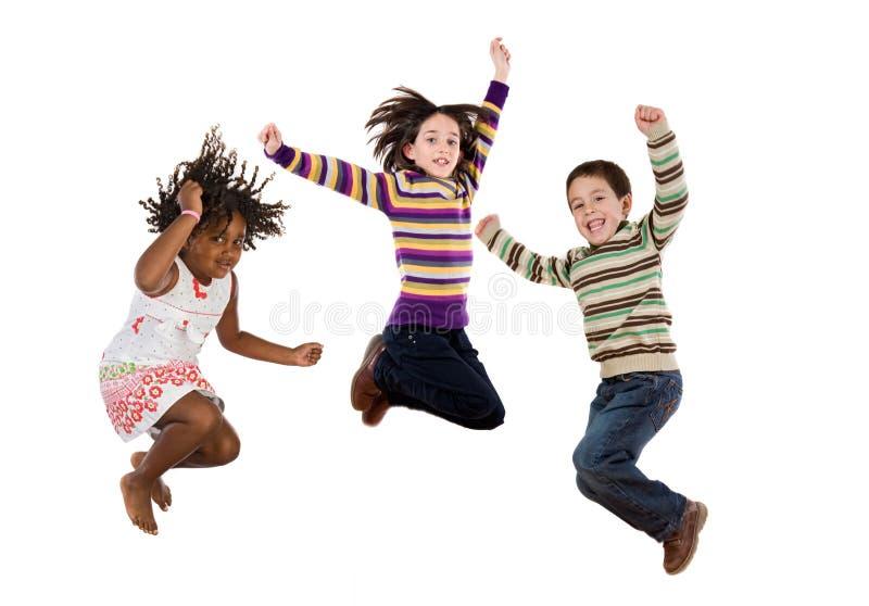 Tres niños felices que saltan inmediatamente imagenes de archivo