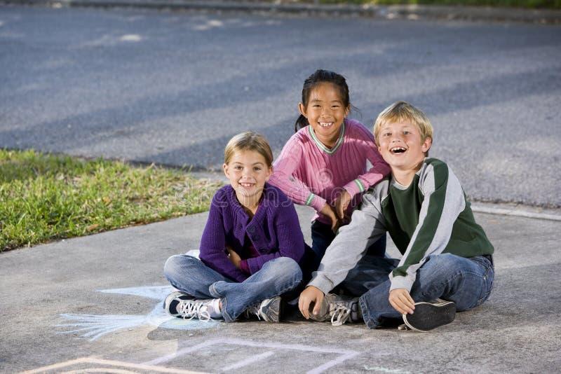 Tres niños felices que se sientan en la calzada fotos de archivo