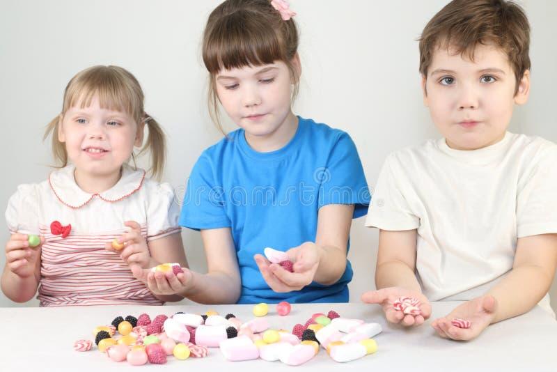 Tres niños felices se sientan con los caramelos y las melcochas fotos de archivo libres de regalías