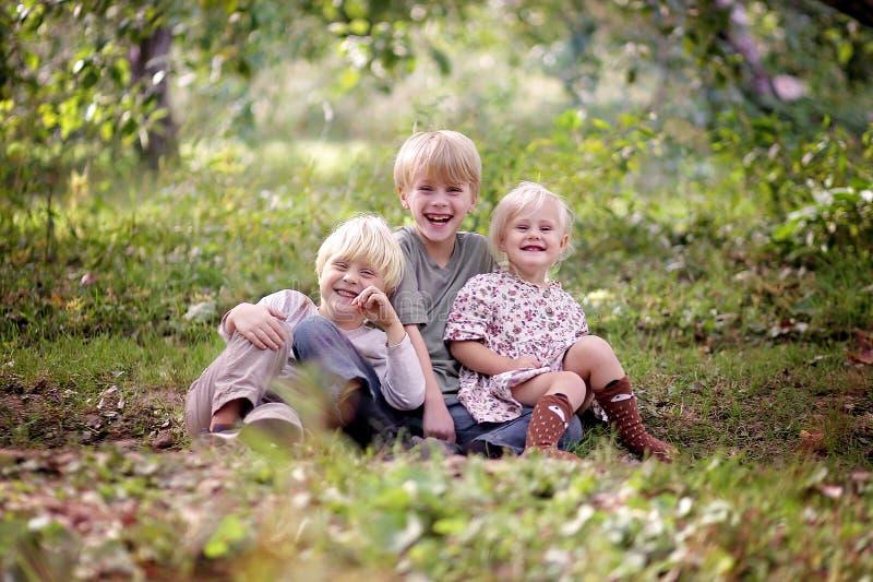 Tres niños jovenes felices que ríen afuera fotos de archivo