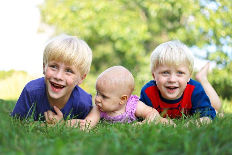Tres niños jovenes felices que ríen afuera imagen de archivo