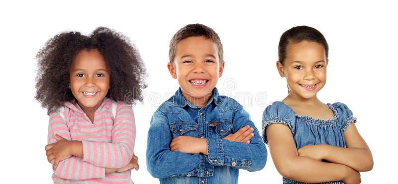 Tres niños latinos que cruzan sus brazos imagen de archivo