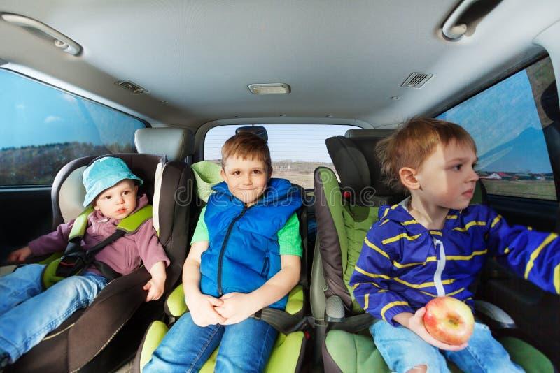Tres niños pequeños que se sientan en asientos de carro de la seguridad imágenes de archivo libres de regalías