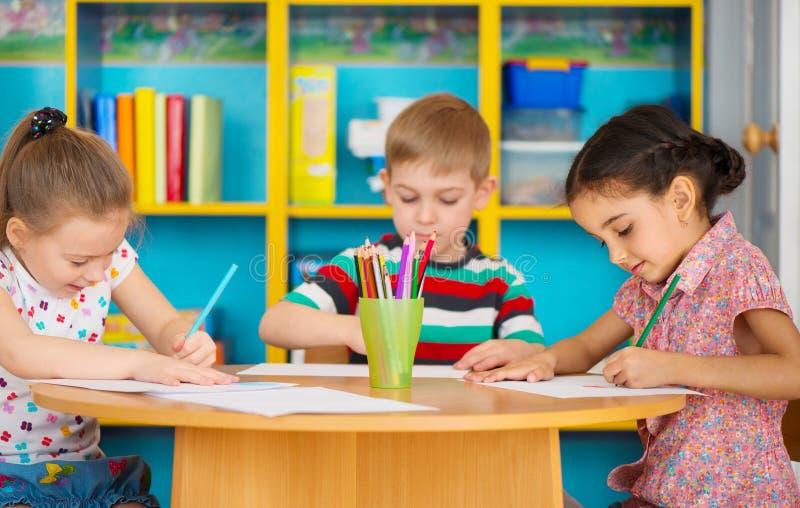 Tres niños preescolares que dibujan en la guardería imagen de archivo