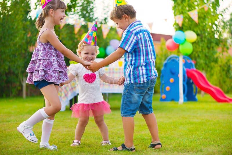 Tres niños que bailan canción con estribillo fotografía de archivo