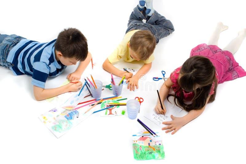 Tres niños que drenan en suelo imágenes de archivo libres de regalías