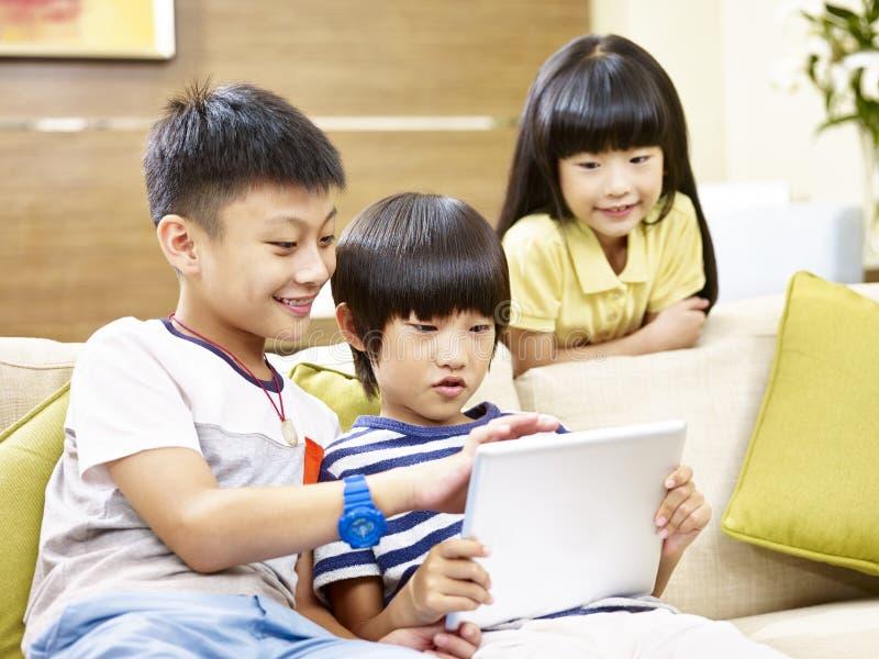 Tres niños que juegan al videojuego usando la tableta digital foto de archivo