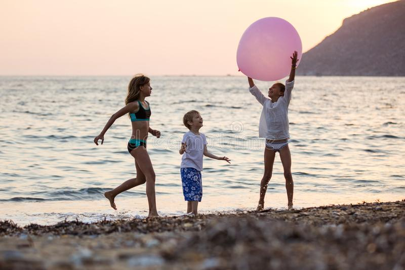 Tres niños que juegan con el globo rosado enorme en la playa en la puesta del sol fotografía de archivo libre de regalías