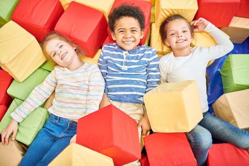 Tres niños que juegan en hoyo de la espuma imágenes de archivo libres de regalías