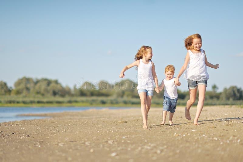 Tres niños que juegan en la playa foto de archivo libre de regalías