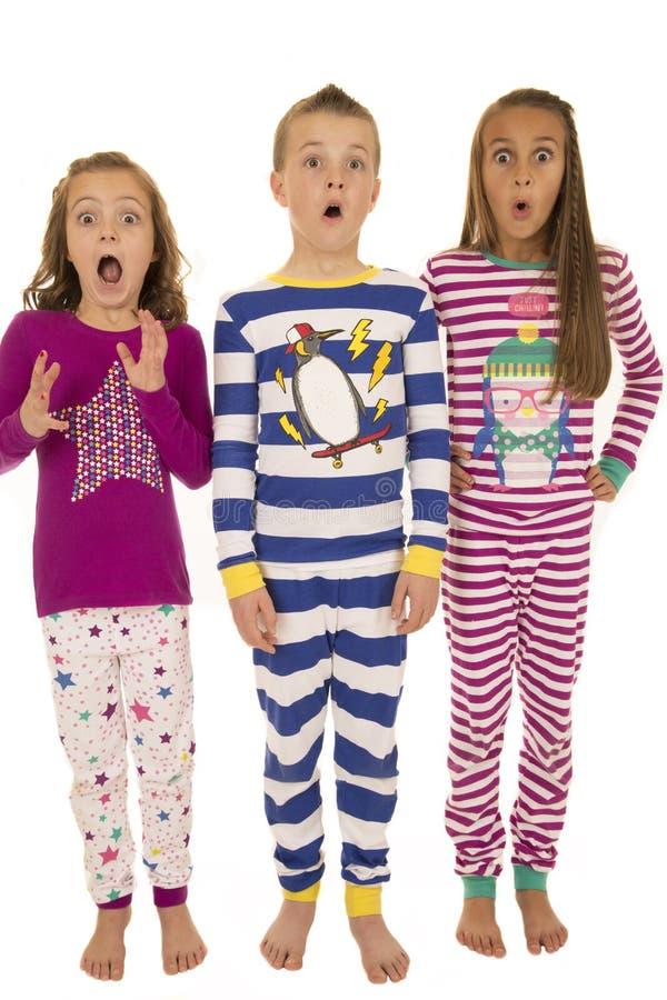 Tres niños que llevan los pijamas del invierno con un exp facial asustado fotos de archivo