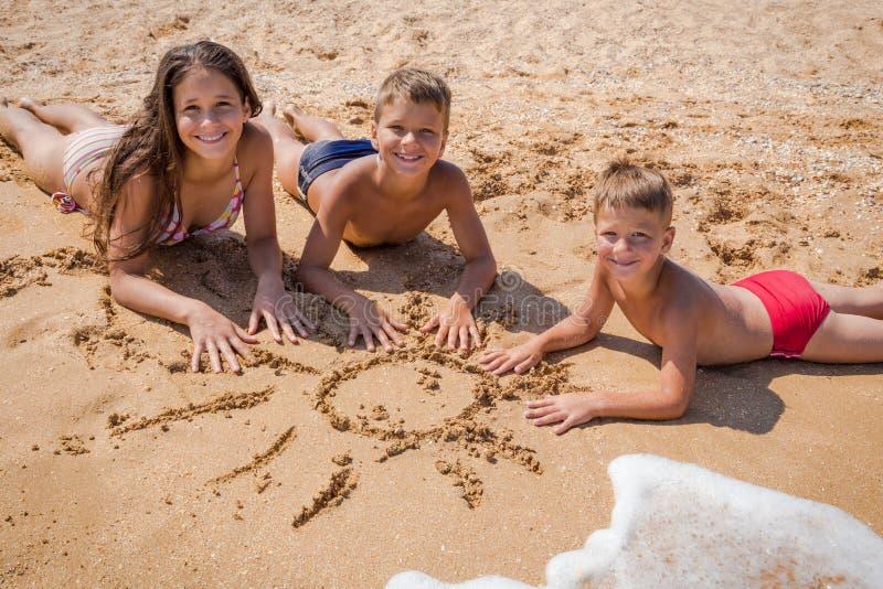 Tres niños que mienten en la playa junto imagenes de archivo