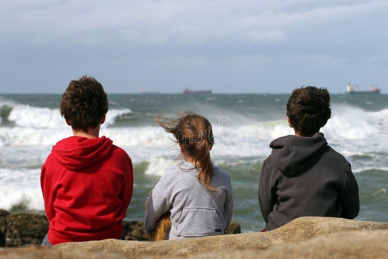 Tres niños que miran hacia fuera al mar imágenes de archivo libres de regalías