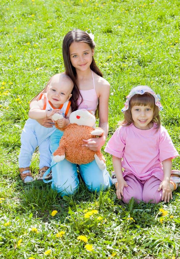 Tres niños que se sientan en la hierba imagen de archivo libre de regalías