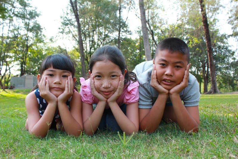 Tres niños que tienen buen tiempo imagenes de archivo