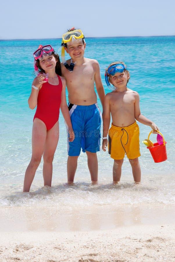 Tres niños que vadean en el océano fotografía de archivo