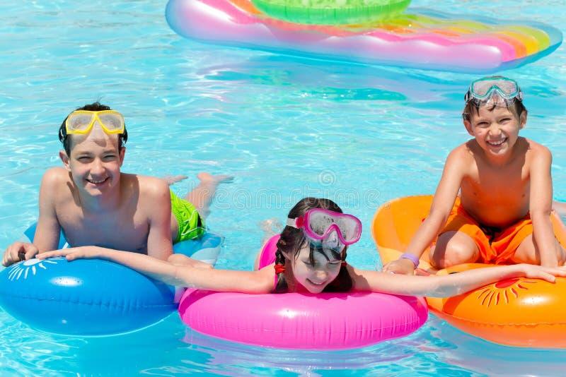 Tres niños sonrientes en piscina imagen de archivo libre de regalías