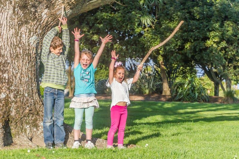 Tres niños sonrientes felices jovenes que caminan en parque imagen de archivo