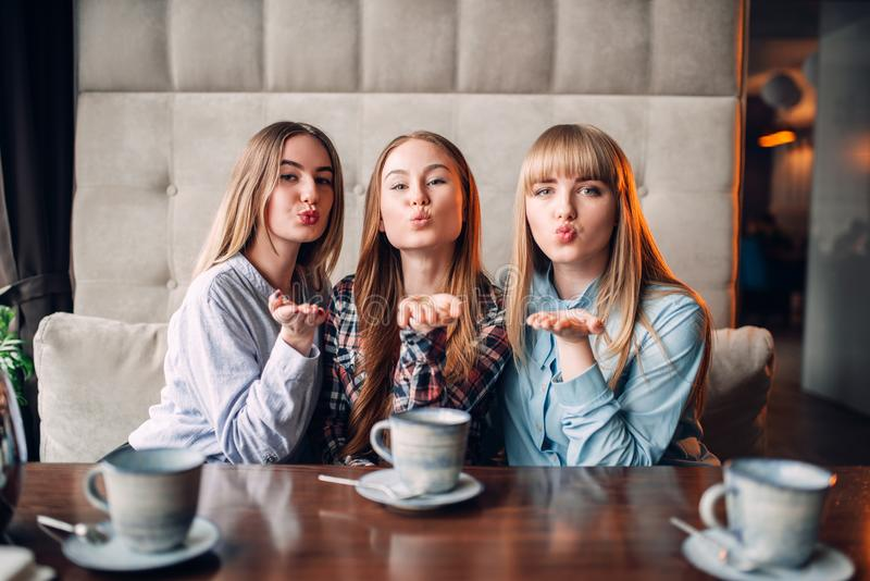 Tres novias atractivas soplan un beso en café imagenes de archivo