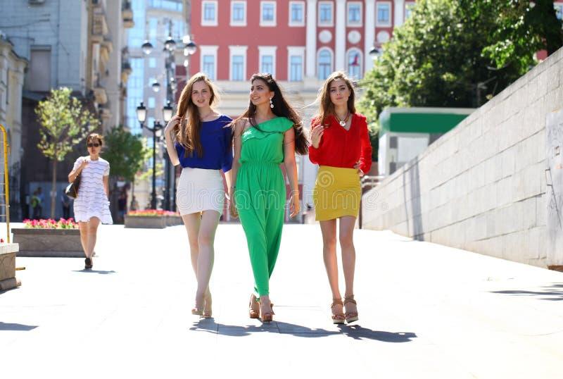 Tres novias hermosas de las mujeres jovenes caminan en una calle del verano fotos de archivo libres de regalías