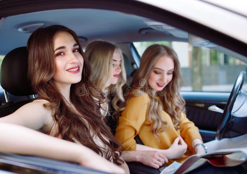 Tres novias jovenes que viajan en un coche imagenes de archivo