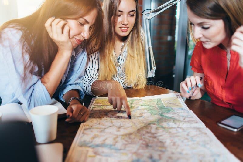 Tres novias que planean sus vacaciones que se sientan en la tabla alrededor del mapa que elige el destino foto de archivo