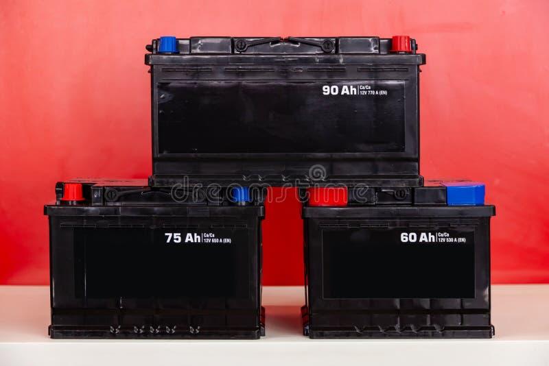 Tres nuevas baterías recargables negras para 60, 75, 95 amperios hora, pirámide del soporte en uno a en un fondo rojo con blanco foto de archivo libre de regalías