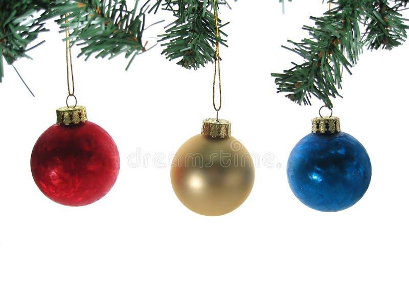 Tres ornamentos de la bola de la Navidad con las ramificaciones de árbol aisladas. fotografía de archivo