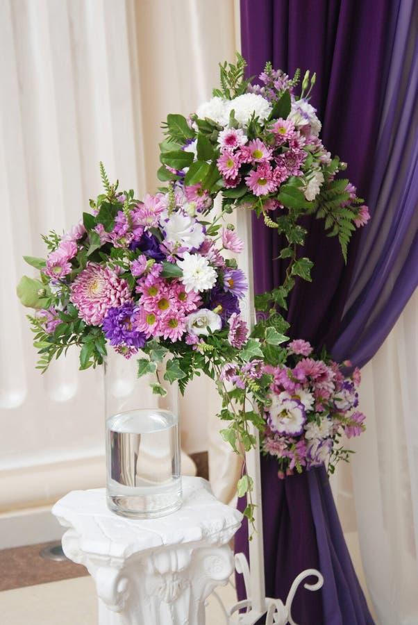 Tres púrpuras y centro de flores rosado del arreglo de la boda Día de boda Florero con las flores Imagen vertical fotos de archivo libres de regalías