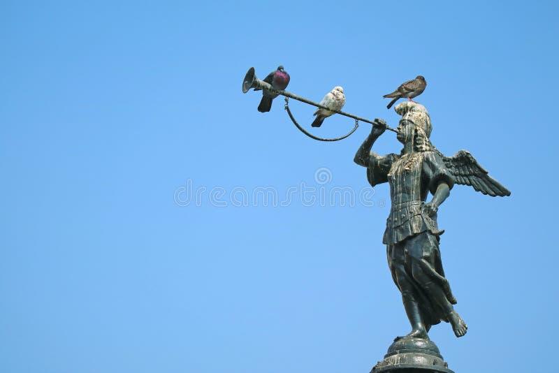 Tres palomas que se relajan en la estatua histórica del ángel de la fama en la fuente en el alcalde de la plaza en Lima, Perú fotografía de archivo