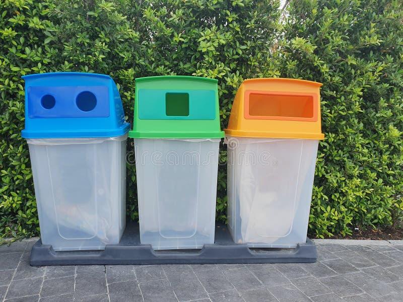 Tres papeleras de reciclaje en el lugar público para la colección de materiales fotos de archivo libres de regalías