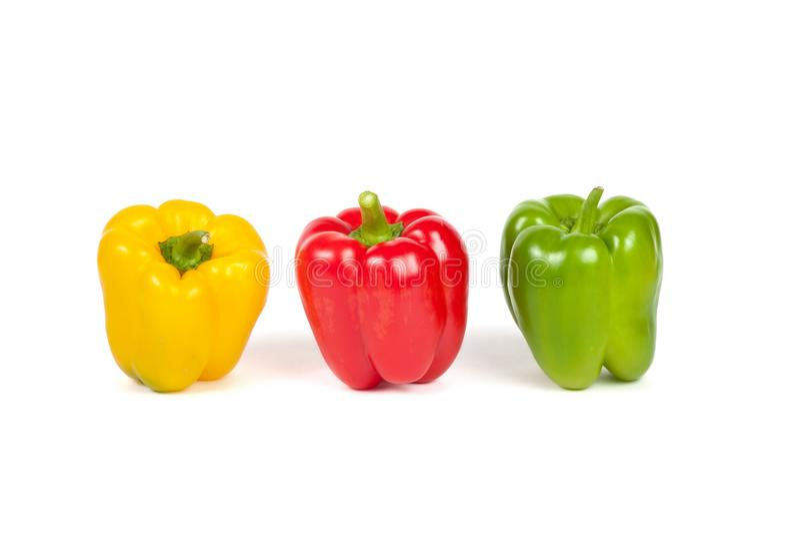 Tres paprikas amarillas, rojas, verdes dulces sazonan con pimienta en blanco imagen de archivo
