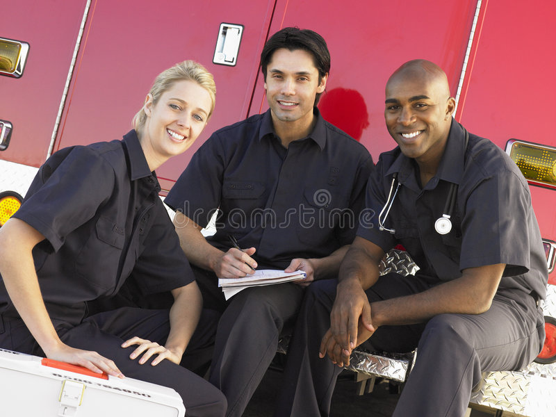 Tres paramédicos que charlan en ambulancia imagen de archivo libre de regalías