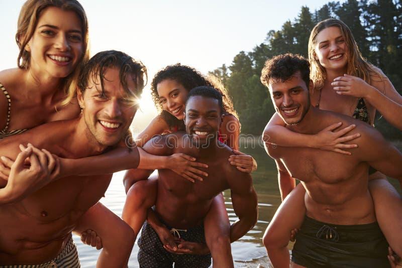 Tres pares adultos jovenes que llevan a cuestas en un lago, cierre para arriba fotos de archivo