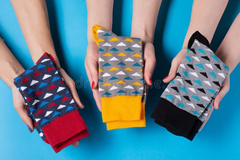 Tres pares de manos femeninas llevan a cabo suavemente calcetines doblados, concepto, la presentación o la oferta imágenes de archivo libres de regalías