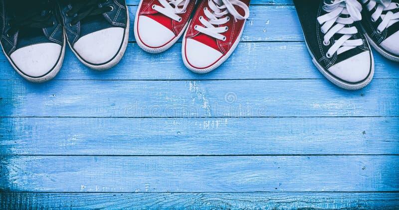 Tres pares de zapatillas de deporte que llevan en una superficie de madera azul, top VI foto de archivo libre de regalías