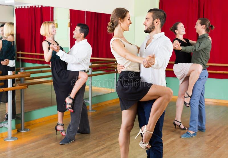 Tres pares felices que bailan tango fotografía de archivo