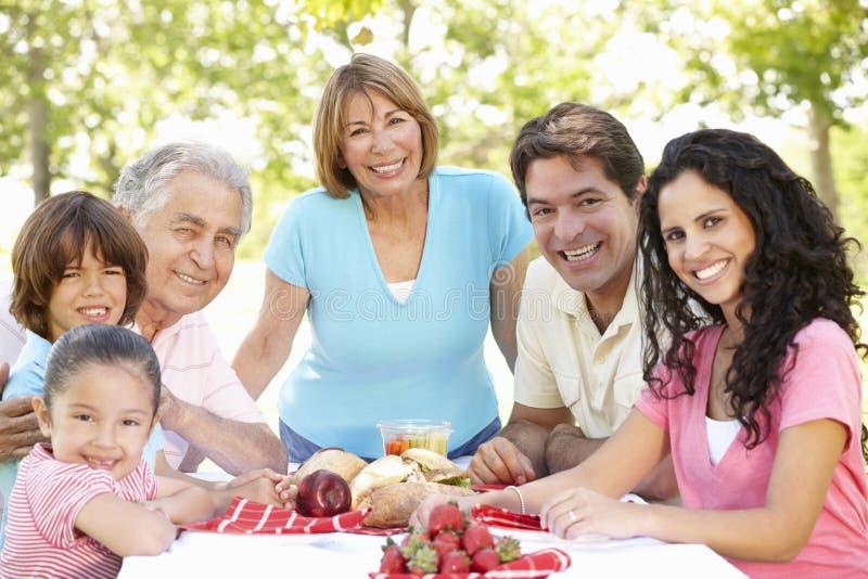 Tres pares hispánicos de la generación que disfrutan de comida campestre en parque fotografía de archivo