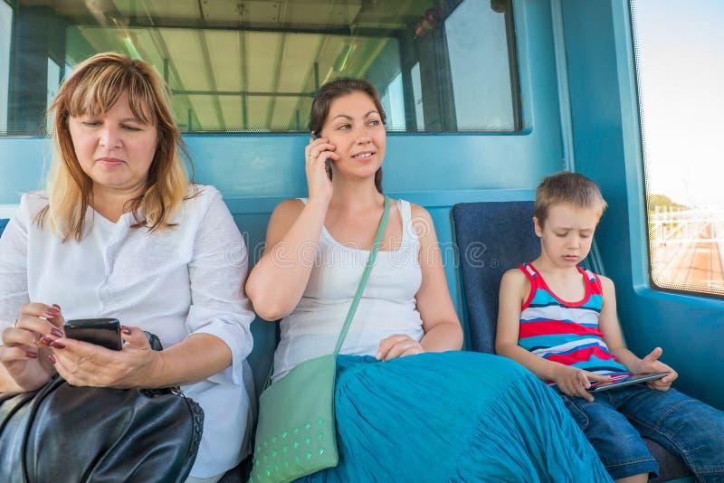 Tres pasajeros de todas las edades en el metro del tren imagenes de archivo