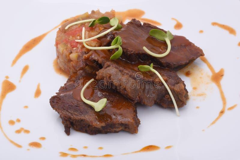 Tres pedazos de cocinado asaron a la parrilla la carne jugosa, caramelizada Con el guisado vegetal fotos de archivo