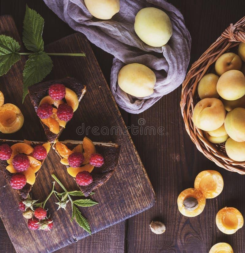 Tres pedazos de pastel de queso con el albaricoque y la frambuesa en un tablero de madera, cerca de la fruta fresca imagenes de archivo