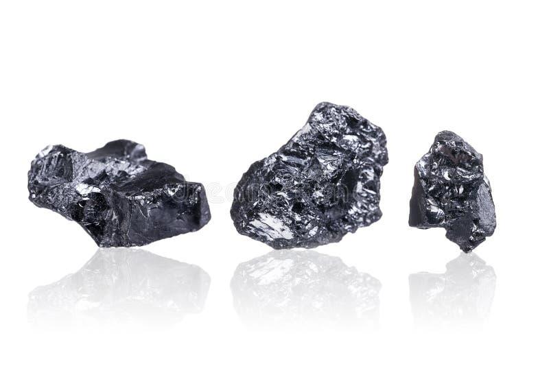 Tres pedazos de un pequeño carbón de antracita, en blanco fotos de archivo