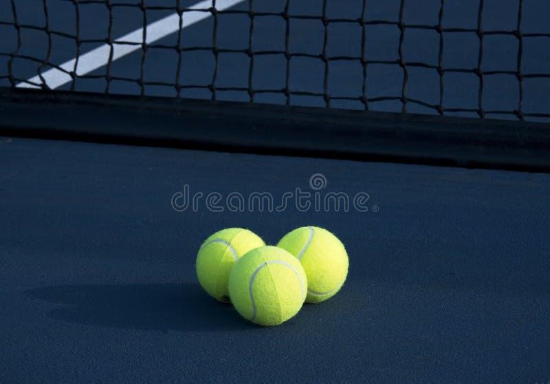 Tres pelotas de tenis en una pista de tenis imagenes de archivo