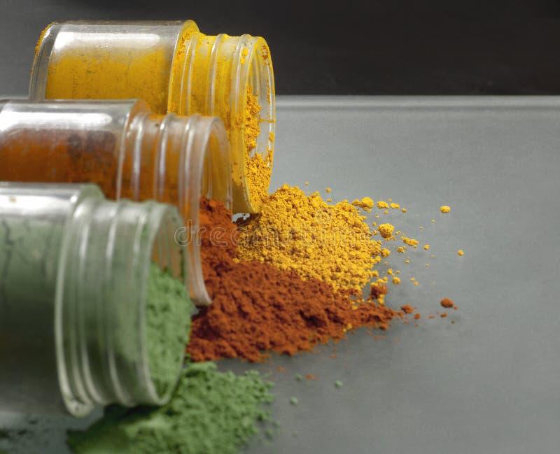 Tres pequeñas botellas llenadas de los polvos coloridos fotografía de archivo