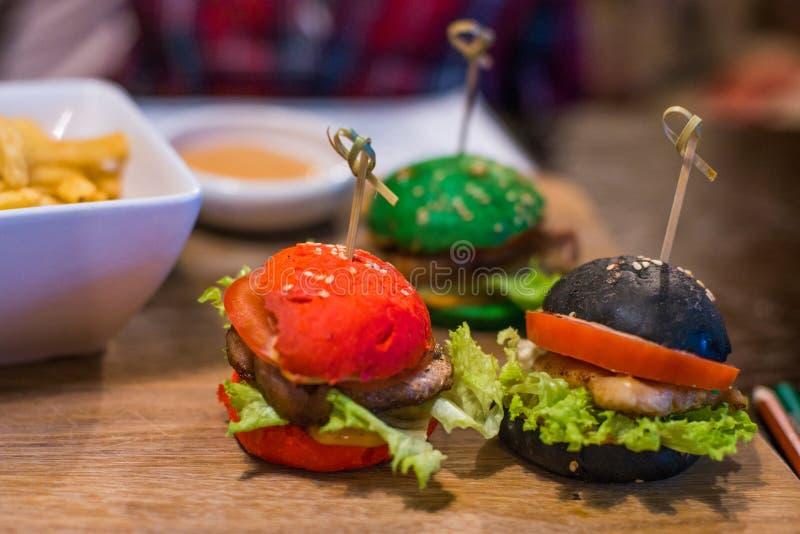 Tres pequeñas hamburguesas para los niños en el restaurante fotografía de archivo libre de regalías
