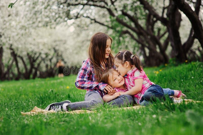Tres pequeñas hermanas que se divierten mucho que juega junto al aire libre en parque del verano el vacaciones fotos de archivo