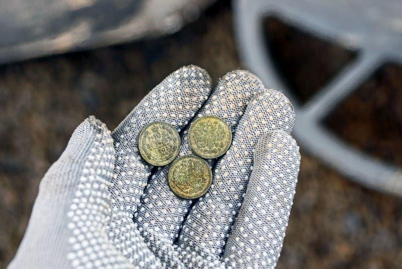 Tres pequeñas monedas de plata en una palma abierta en un guante gris fotos de archivo libres de regalías